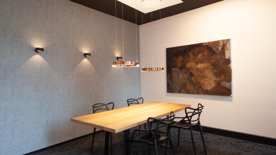 Occhio Ausstellung bei Conceptlicht: Wandstrahler und Hängeleuchte über dem Esstisch
